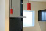 赤いペンダントライトをアクセントにしたキッチンとシックな和室があるお家