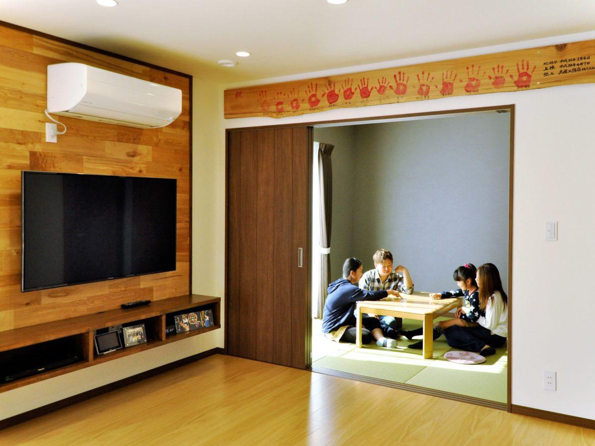 親子で楽しく料理できる広々キッチンと木の温かみを感じるリビングがあるお家